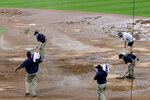 Grounds crew members work on the rain-soaked field during the 10th inning of a baseball game between the Cleveland Indians and the Chicago White Sox on Sunday, Aug. 9, 2020, in Chicago. (AP Photo/Nam Y. Huh)