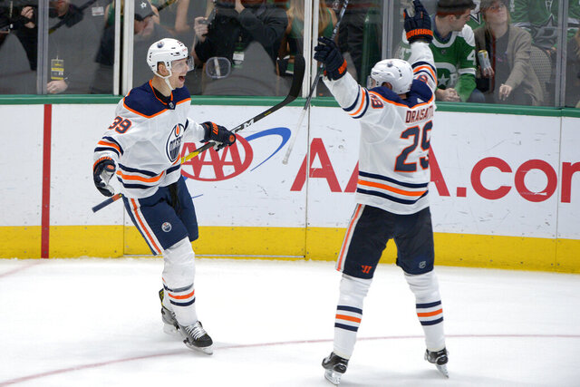 Edmonton Oilers right wing Alex Chiasson (39) and center Leon Draisaitl (29) celebrate Chiasson's overtime goal against the Dallas Stars in an NHL hockey game in Dallas, Tuesday, March 3, 2020. The Oilers won 2-1. (AP Photo/Matt Strasen)