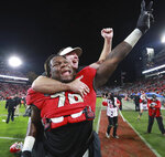 Georgia head coach Kirby Smart jumps on the back of offensive lineman Isaiah Wilson to celebrate beating Texas A&M 19-13 in an NCAA college football game  Saturday, Nov. 23, 2019, in Athens, Ga. (Curtis Compton/Atlanta Journal-Constitution via AP)