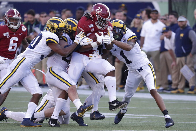 Alabama running back Najee Harris (22) fights for extra yardage as Michigan defensive back Daxton Hill, left, linebacker Jordan Glasgow, second from left, and defensive back Ambry Thomas (1) try to stop him during the second half of the Citrus Bowl NCAA college football game, Wednesday, Jan. 1, 2020, in Orlando, Fla. (AP Photo/John Raoux)