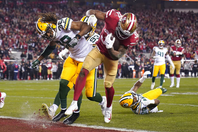 San Francisco 49ers running back Raheem Mostert, center right, scores a touchdown next to Green Bay Packers cornerback Tramon Williams during the second half of the NFL NFC Championship football game Sunday, Jan. 19, 2020, in Santa Clara, Calif. (AP Photo/Tony Avelar)