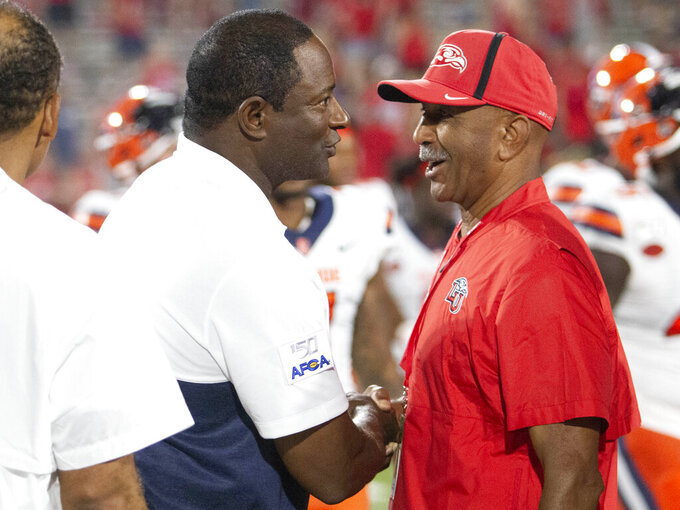 Syracuse coach Dino Babers, left, shakes hands with Ed Gomes, Liberty director of spiritual development, following an NCAA college football game in Lynchburg, Va., Saturday, Aug. 31, 2019. (AP Photo/Matt Bell)
