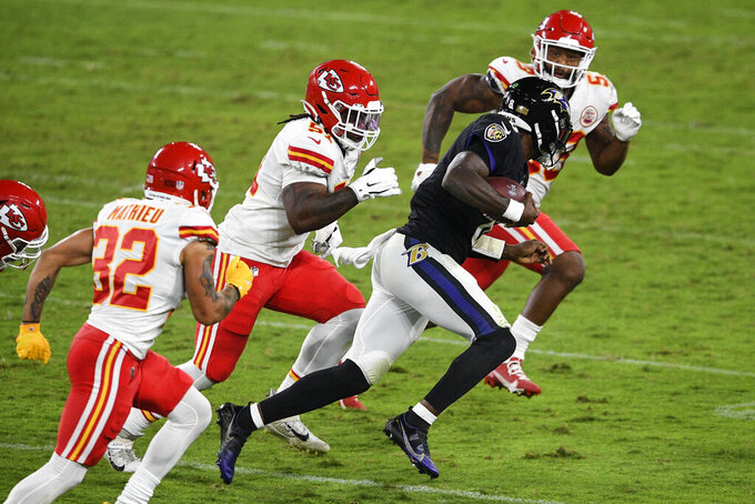 Baltimore Ravens quarterback Lamar Jackson (8) scrambles as he is pursued by Kansas City Chiefs strong safety Tyrann Mathieu, left, defensive end Michael Danna and inside linebacker Anthony Hitchens during the second half of an NFL football game Monday, Sept. 28, 2020, in Baltimore. (AP Photo/Nick Wass)