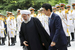 Japanese Prime Minister Shinzo Abe, right, reviews an honor guard as he is welcomed by Iranian President Hassan Rouhani, in an official arrival ceremony at the Saadabad Palace in Tehran, Iran, Wednesday, June 12, 2019. The Japanese leader is in Tehran on an mission to calm tensions between the U.S. and Iran. (AP Photo/Ebrahim Noroozi)