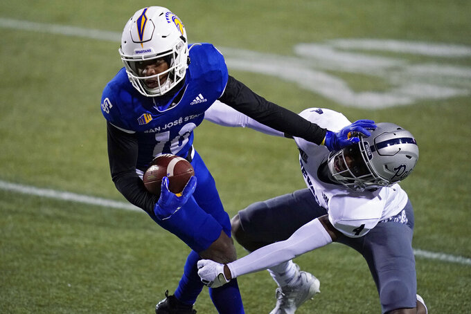 FILE - In this Friday, Dec. 11, 2020 file photo, Nevada defensive back EJ Muhammad (4) tackles San Jose State wide receiver Tre Walker (10) during the second half of an NCAA college football game in Las Vegas. No. 25 San Jose State will face perennial conference powerhouse Boise State in the Mountain West championship on Saturday, Dec. 19, 2020 in Las Vegas. The game is usually played on the higher seed's home field but this year it will be held at Sam Boyd Stadium. (AP Photo/John Locher, File)