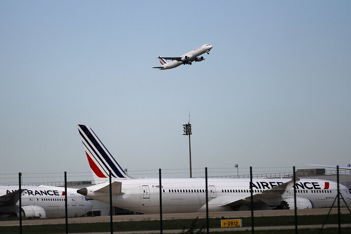 FILE- This April 11, 2018 photo shows Air France planes parked on the tarmac at Paris Charles de Gaulle airport, in Roissy, near Paris. A French association of victims says investigating magistrates dropped the case against Air France and Airbus in the 2009 crash of a flight from Rio de Janeiro to Paris that killed all 228 people aboard. (AP Photo/Christophe Ena, File)