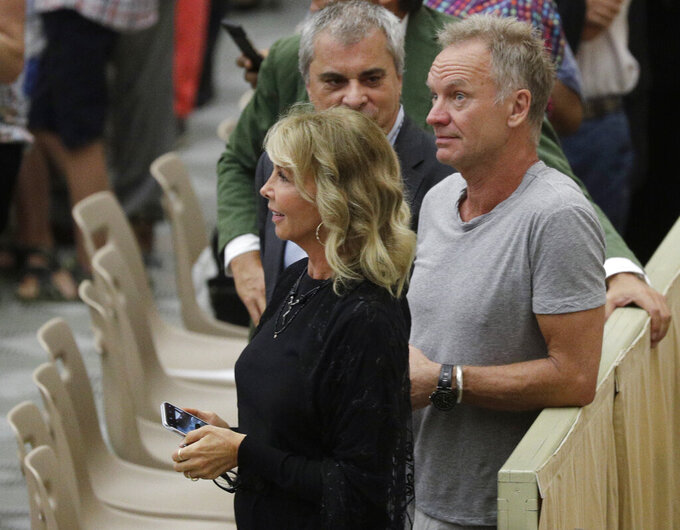 """FILE - In this photo taken on Aug. 8, 2018, British musician Gordon Sumner, better known as Sting, right, and his wife Trudie Styler, attend the weekly general audience of Pope Francis at the Vatican. The family of a late duke who sold Sting his Tuscan winery says the singer's apology for comments the family deems slanderous falls flat. The dispute exploded in Italian newspapers when Sting told Corriere della Sera's weekly magazine Sette on Aug. 13 that he was persuaded to buy the estate near Florence in 1997 after tasting an """"excellent"""" glass of red wine offered by the owner, Simone Vincenzo Velluti Zati di San Clemente, only to learn later that it was a Barolo from the Piedmont region and not a Tuscan Chianti at all. (AP Photo/Gregorio Borgia)"""