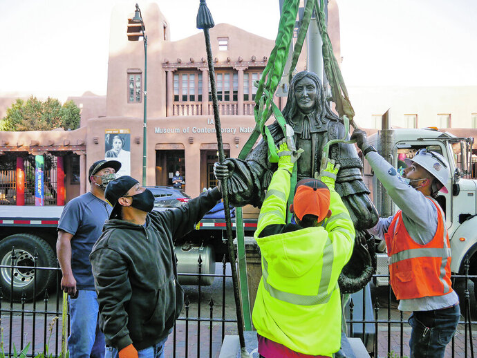 Workers fit harnesses around a statue of Don Diego de Vargas during the statue's removal from Cathedral Park in Santa Fe, N.M., Thursday, June 18, 2020. Crews in Santa Fe on Thursday removed the statue of the Spanish territorial governor from the city park and two other markers were slated to come down as monuments to historical figures were being dismantled across the country. (Matt Dahlseid/Santa Fe New Mexican via AP)