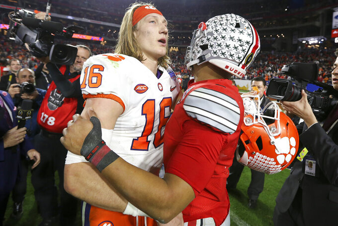 Clemson quarterback Trevor Lawrence, left, and Ohio State quarterback Justin Fields meet after the Fiesta Bowl NCAA college football playoff semifinal Saturday, Dec. 28, 2019, in Glendale, Ariz. (AP Photo/Ross D. Franklin)