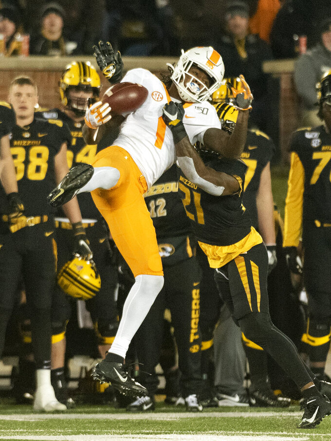 Tennessee wide receiver Marquez Callaway, left, is hit by Missouri defensive back Christian Holmes, right, as he tries to catch a pass during the third quarter of an NCAA college football game Saturday, Nov. 23, 2019, in Columbia, Mo. Holmes was flagged for pass interference on the play. (AP Photo/L.G. Patterson)