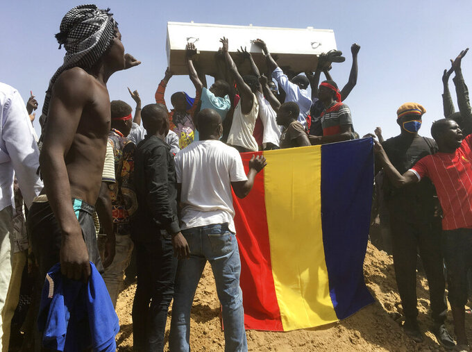 Mourners chanting as some hold the coffin during the funeral of one of the victims who was killed earlier this week, at a cemetery in N'Djamena, Chad, Saturday, May 1, 2021. Hundreds of chanting mourners carrying Chadian flags gathered Saturday to bury victims who were shot dead earlier this week amid demonstrations against the country's new military government.(AP Photo/Sunday Alamba)