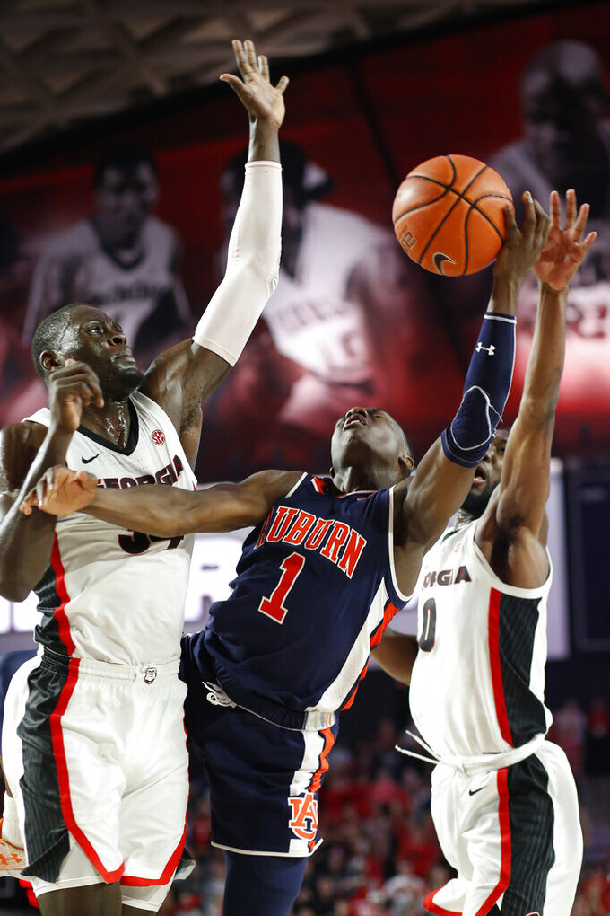 Auburn guard Jared Harper (1) is fouled as Georgia forward Derek Ogbeide (34) and guard William Jackson II (0) defend during an NCAA college basketball game Wednesday, Feb. 27, 2019, in Athens, Ga. (Joshua L. Jones/Athens Banner-Herald via AP)