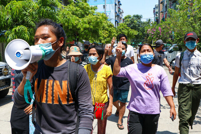 Young demonstrators flash the three-fingered symbol of resistance as they march in Yangon, Myanmar, Saturday, April 10, 2021. Security forces in Myanmar cracked down heavily again on anti-coup protesters Friday even as the military downplayed reports of state violence.(AP Photo)