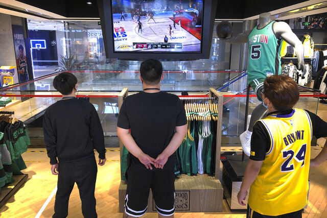 Employees watch a live broadcast of Game 5 of the NBA Finals at an NBA store in Beijing, Saturday, Oct. 10, 2020. The NBA is returning to Chinese state television after a one-year absence. CCTV announced Friday that it would air Game 5 of the NBA Finals between the Los Angeles Lakers and Miami Heat — the first time that the league would appear on the network since the rift that started when Houston Rockets general manager Daryl Morey tweeted support for anti-government protesters in Hong Kong. (AP Photo/Mark Schiefelbein)