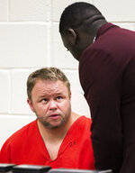 Michael W. Jones Jr. talks with a public defender during his initial appearance at the Marion County Jail courtroom, Thursday, Sept. 19, 2019, in Ocala, Fla. Jones, suspected of killing his wife and four children and driving their bodies into Georgia, returned to Florida to face murder charges. (Doug Engle/Star-Banner via AP)