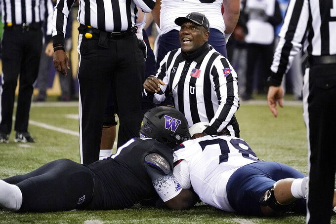 Umpire Gregory Adams looks up to make a call on a fumble recovery as Washington's Josiah Bronson, left, and Donovan Laie continue to fight for possession during the first half of an NCAA college football game Saturday, Nov. 21, 2020, in Seattle. Washington won the call. (AP Photo/Elaine Thompson)