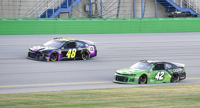 Jimmie Johnson (48) drives next to Kyle Larson (42) during the NASCAR Cup Series auto race at Kentucky Speedway in Sparta, Ky., Saturday, July 13, 2019. (AP Photo/Timothy D. Easley)