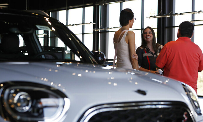 FILE - In this Aug. 30, 2018, file photo, a salesperson, center, confers with two customers interested in the 2018 Countryman on display in the showroom of a Mini dealership in Highlands Ranch, Colo. Choosing a smaller vehicle, leasing, or buying a used vehicle are a few of the recommended methods in lowering a car payment. (AP Photo/David Zalubowski, File)