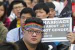 FILE - In this Dec. 10, 2016, file photo, a supporter of LGBT and human rights holds a slogan during a rally supporting a proposal to allow same-sex marriage in Taipei, Taiwan. Taiwanese legislators are scheduled to decide Friday on legalizing same-sex marriage, marking a potential first in Asia. (AP Photo/Chiang Ying-ying, File)
