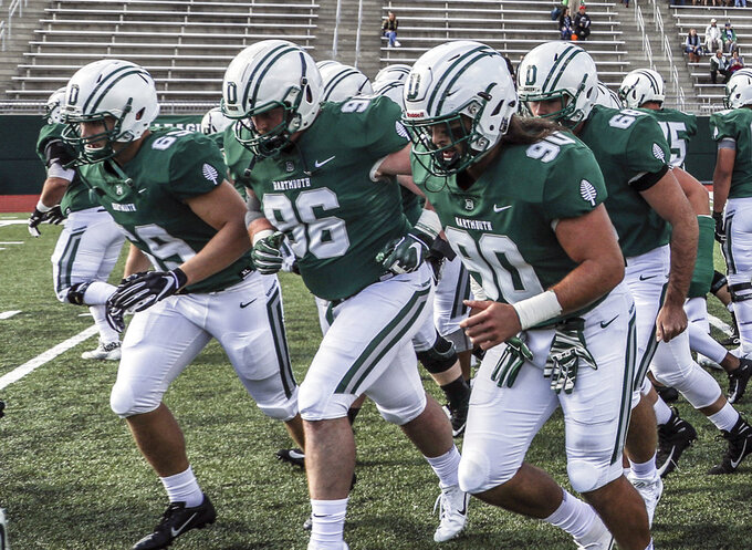 In this Sept. 29, 2018, photo provided by Dartmouth College, Seth Simmer (96) is flanked by Tommy Ciesla (69) and Niko Lalos (90) during warmups before an NCAA college football game between Dartmouth and Penn in Hanover, N.H. During his freshman season at Dartmouth, Seth Simmer was having trouble hearing the linebackers call signals from his defensive tackle spot just a few yards away. What was first diagnosed as an ear infection brought on by a severe head cold turned out to be a brain tumor that was making him deaf in his left ear. Simmer is one of 30 nominees for the Mayo Clinic Comeback Player of the Year Award. (Tom McNeill/Dartmouth College via AP)