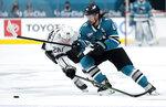 San Jose Sharks defenseman Erik Karlsson (65) moves the puck past Los Angeles Kings center Jaret Anderson-Dolan (28) during the third period of an NHL hockey game Saturday, April 10, 2021, in San Jose, Calif. The Kings won 4-2. (AP Photo/Tony Avelar)