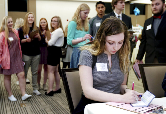 FILE - In this April 5, 2017, file photo, Memorial High School senior Taylor Wicks figures which life insurance plan to purchase during the Eau Claire Area Chamber of Commerce's Real Life Academy at the Lismore Hotel in Eau Claire, Wis. A rise in freelancing, coupled with an increasing interest in flexible employment from millennial and Gen Z workers, could signal a change in how Americans build and calculate life insurance plans. (Marisa Wojcik/The Eau Claire Leader-Telegram via AP, File)