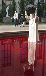 Visitors to the National Museum walk past a new statue of the late pope, St. John Paul II, throwing a stone at a