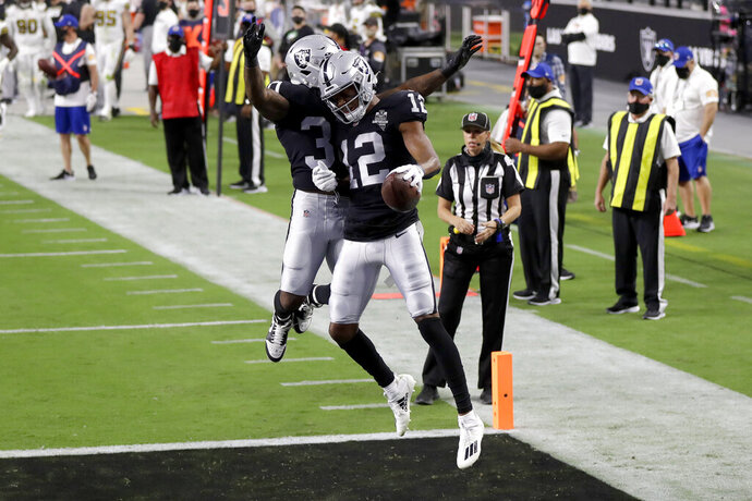 Las Vegas Raiders running back Jalen Richard, left, celebrates after wide receiver Zay Jones (12) scored a touchdown against the New Orleans Saints during the first half of an NFL football game, Monday, Sept. 21, 2020, in Las Vegas. (AP Photo/Isaac Brekken)