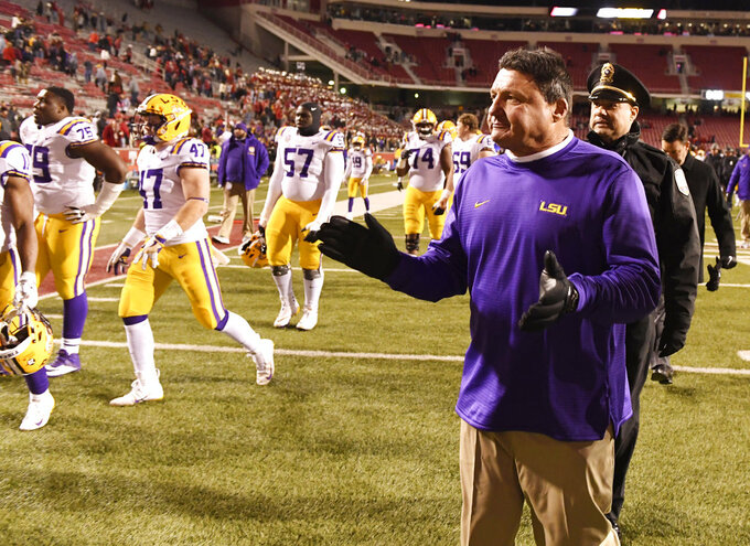 LSU coach Ed Orgeron celebrates with his team after beating Arkansas 24-17 during an NCAA college football game, Saturday, Nov. 10, 2018, in Fayetteville, Ark. (AP Photo/Michael Woods)