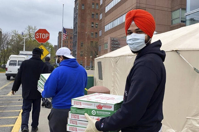 In this April 7, 2020, handout photo, Japneet Singh, right, delivers pizza to health care workers at Kings County Hospital in the Brooklyn borough of New York.  Singh estimates 1,000 pizzas were delivered to essential workers since the end of March. (Courtesy of the New York Sikh Council via AP)