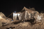 A tent where smugglers stay while building fishing boats to be used to carry migrants to the Canary Islands, is set up in a remote part of the desert out of the town of Dakhla in Morocco-administered Western Sahara, Tuesday, Dec. 22, 2020. (AP Photo/Mosa'ab Elshamy)