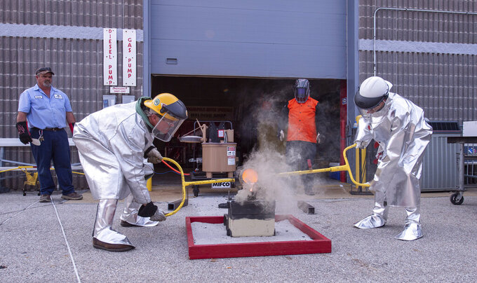 Winner of this year's Indianapolis 500 auto race, Helio Castroneves, right, pours molten bronze into a brick mold engraved with his name to commemorate his fourth winning of the race, Tuesday, July 20, 2021, at the Indianapolis Motor Speedway in Indianapolis. The brick will be laid among other bricks that mark the start/finish line of the course. Castroneves previously won the race in 2001, 2002, and 2009. Bud Tucker, a welder at the track, created the mold and assists Castroneves with the pouring. (AP Photo/Doug McSchooler)