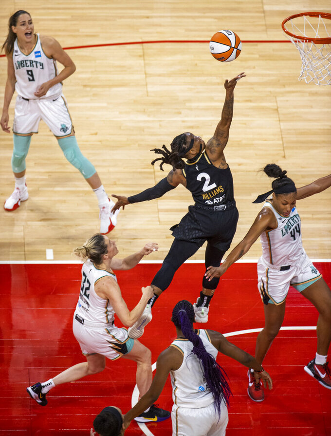 Las Vegas Aces guard Riquna Williams (2) jumps for a finger roll over New York Liberty guard Sami Whitcomb (32) and guard/forward Betnijah Laney (44) during the second quarter of a WNBA basketball game Thursday, June 17, 2021, in Las Vegas. (L.E. Baskow/Las Vegas Review-Journal via AP)
