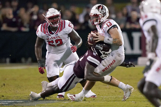 North Carolina State quarterback Devin Leary (13) is sacked by Mississippi State defensive end Randy Charlton (5) during the second half of an NCAA college football game in Starkville, Miss., Saturday, Sept. 11, 2021. Mississippi State won 24-10. (AP Photo/Rogelio V. Solis)