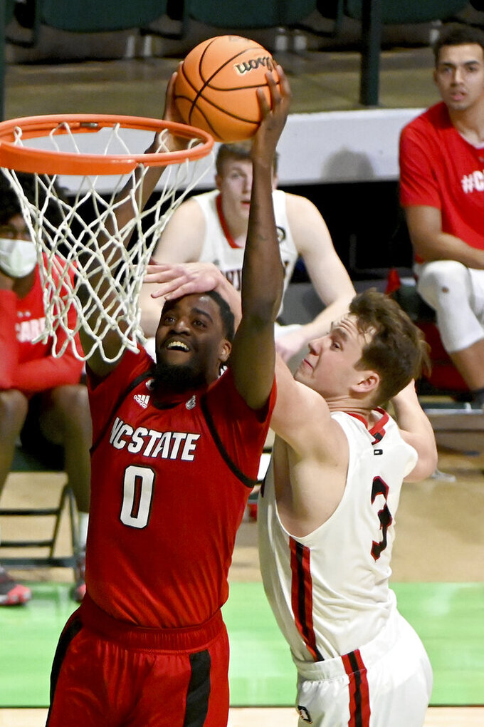 North Carolina State forward DJ Funderburk (0) dunks over Davidson forward Sam Mennenga (3) in the first half of an NCAA college basketball game in the first round of the NIT, Thursday, March 18, 2021, in Denton, Texas. (AP Photo/Matt Strasen)