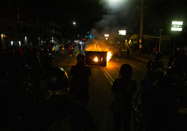 A waste receptacle is set on fire near the Portland Police Association building during a protest in Portland, Ore., on Tuesday, Aug. 4, 2020.  A riot was declared early Wednesday during demonstrations in Portland after authorities said people set fires and barricaded public roadways.(Dave Killen /The Oregonian via AP)