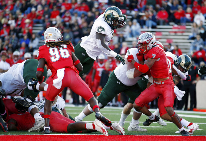 Colorado State running back David Bailey, center, dives into the end zone for a touchdown against New Mexico during the first half of an NCAA college football game, Saturday, Oct. 16, 2021, in Albuquerque, N.M. (AP Photo/Andres Leighton)