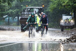 Three cyclists ride through water on flooded Highway 54 in Rummenohl, western Germany, Wednesday, July 14, 2021. Storms caused widespread flooding across central Germany overnight, with authorities warning that more rain is on the way. ( Guettler/dpa via AP)