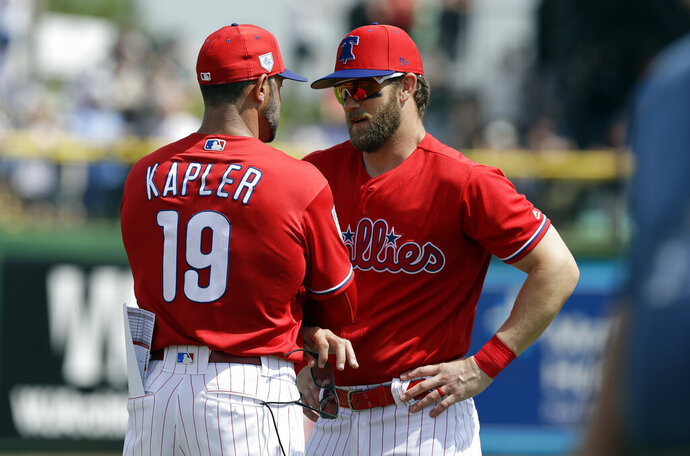 Philadelphia Phillies manager Gabe Kapler (19) talks to Bryce Harper before a spring training baseball game against the Tampa Bay Rays Monday, March 11, 2019, in Clearwater, Fla. (AP Photo/Chris O'Meara)