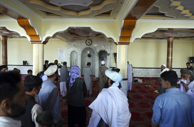 People stand inside a mosque after a bomb explosion in Shakar Dara district of Kabul, Afghanistan, Friday, May 14, 2021. A bomb ripped through a mosque in northern Kabul during Friday prayers killing 12 worshippers, Afghan police said. (AP Photo/Rahmat Gul)