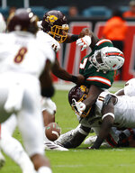 Miami offensive lineman John Campbell Jr. (74), Central Michigan linebacker Troy Hairston (45) and Central Michigan defensive lineman LaQuan Johnson (11) all go for the fumble during the first half of an NCAA college football game, Saturday, Sept. 21, 2019, in Miami Gardens, Fla. (AP Photo/Brynn Anderson)