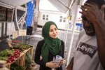 In this Monday, Aug. 19, 2019, photo, dietitian Heba Abdel Latief, right, talks to her patient, Richard Ware, at Inner-city Muslim Action Network's (IMAN) farmers market in Chicago. IMAN offers free of charge dietitian visits at their health clinic. Atlanta, Chicago and other large cities across the country are taking a multi-pronged approach to bringing healthy diets to