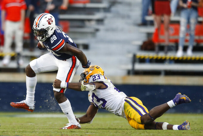 Auburn running back Mark-Antony Richards (28) is tackled by LSU linebacker Micah Baskerville (23) as he carries the ball during the second half of an NCAA college football game on Saturday, Oct. 31, 2020, in Auburn, Ala. (AP Photo/Butch Dill)