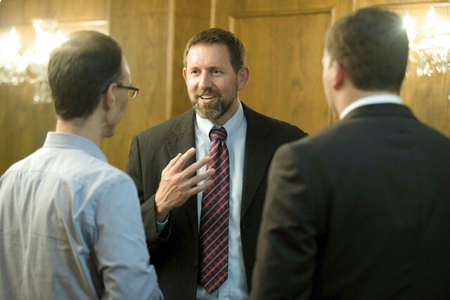 """FILE - In this Sept. 23, 2014, file photo, former Montana Solicitor General Lawrence VanDyke, center, talks with law students Jason Collins, left, and Tyler Dugger before a Montana Supreme Court candidate forum at the University of Montana in Missoula, Mont. The Senate has confirmed VanDyke as a federal appeals court judge despite a """"not qualified"""" rating from the American Bar Association and sharp opposition from his home-state senators. (AP Photo/Lido Vizzutti, File)"""