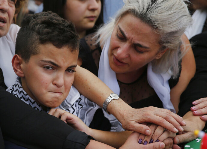 Omar, left, and his mother Lara, the son and the wife of of Alaa Abu Fakher, who was killed by a Lebanese soldier in Tuesday night protests south of Beirut, attend his funeral, in Choueifat neighborhood, Lebanon, Thursday, Nov. 14, 2019. For nearly a month, the popular protests engulfing Lebanon have been startlingly peaceful. But the shooting death of Fakher, a 38-year-old father by a soldier, the first such fatality in the unrest, points to the dangerous, dark turn the country could be heading into. (AP Photo/Hussein Malla)