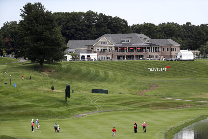 The clubhouse is visible as golfers play through with the absence of fans because of the new coronavirus restrictions during the first round of the Travelers Championship golf tournament at TPC River Highlands, Thursday, June 25, 2020, in Cromwell, Conn. (AP Photo/Frank Franklin II)
