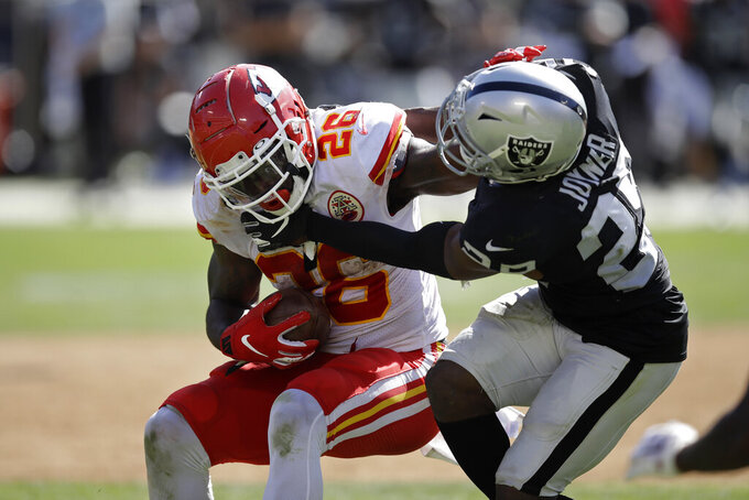 Kansas City Chiefs running back Damien Williams tries to break away from Oakland Raiders free safety Lamarcus Joyner, right, during the second half of an NFL football game Sunday, Sept. 15, 2019, in Oakland, Calif. (AP Photo/Ben Margot)