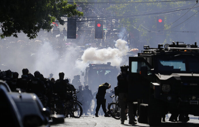 FILE - In this July 25, 2020, file photo, smoke rises as police clash with protester during a Black Lives Matter protest near the Seattle Police East Precinct headquarters in Seattle. A Seattle police officer who threw a tear gas canister that hit a reporter and other officers who threw blast balls that hit individuals during last summer's Black Lives Matter protests violated policies, according to new reports from an independent agency tasked with investigating police misconduct. The agency has released five batches of investigative reports since September, with the latest 22 cases posted Friday, Jan. 15, 2021. (AP Photo/Ted S. Warren, File)
