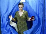 A woman leaves a booth at a polling station during at a parliamentary election in Kiev, Ukraine, Sunday, July 21, 2019. The party of new President Volodymyr Zelenskiy is widely predicted to get the largest share of votes in Sunday's election. (AP Photo/Evgeniy Maloletka)
