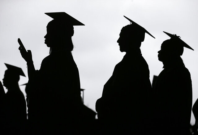 FILE - In this May 17, 2018, file photo, new graduates line up before the start of the Bergen Community College commencement at MetLife Stadium in East Rutherford, N.J. Many new college graduates are struggling to find work as their first student loan payments loom on the horizon. Fewer entry-level jobs are available during the pandemic, and unemployment benefits typically aren't accessible. (AP Photo/Seth Wenig, File)